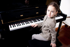 young girl doing piano lesson
