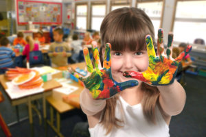 Young School Age Child Painting With Her Hands in Class